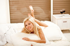 Pretty woman in bed, smiling Stock Photography