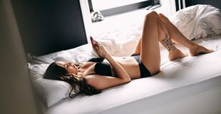 Pretty woman on bed texting with her mobile phone. Stock Photo