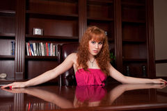 Pretty Woman behind the Desk. Sexy redhead woman in a luxury office Royalty Free Stock Photos