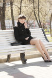 Pretty woman on bench with cellphone Stock Image