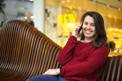 Pretty woman on a bench in mall stock image