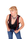 Pretty woman bending with suspenders. A woman in her forties standing in jeans and a black blouse with red Royalty Free Stock Photography