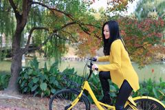 Image of woman with bicycle in a park Royalty Free Stock Image