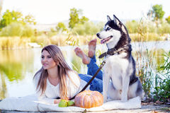 Pretty woman and big dog husky is resting outdoors Stock Photo