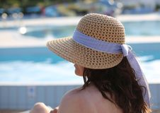 Pretty woman with a big straw hat and she relaxes in the exclusi stock image