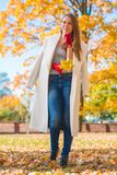 Pretty Woman in Big White Coat Holding Leaves Royalty Free Stock Photos