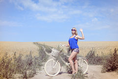 Pretty woman with bike on countryside landscape blue sky background outdoors Stock Photos