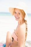 Pretty woman in bikini and beach hat sitting on the beach Stock Image
