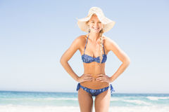 Pretty woman in bikini and beach hat standing on the beach Royalty Free Stock Photography