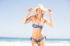 Pretty woman in bikini and beach hat standing on the beach Royalty Free Stock Images