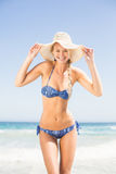 Pretty woman in bikini and beach hat standing on the beach Royalty Free Stock Image