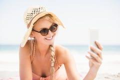 Pretty woman in bikini and sunglasses taking a selfie on the beach Stock Photography