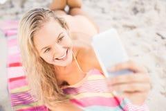 Pretty woman in bikini taking a selfie on the beach Stock Photography
