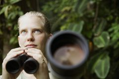 Pretty Woman with Binoculars in the Rain Forest Stock Images