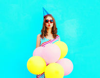Pretty woman in a birthday cap is sends an air kiss holds an air colorful balloons Stock Images
