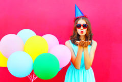 Pretty woman in a birthday cap is sends an air kiss holds an air colorful balloons on pink background Royalty Free Stock Image