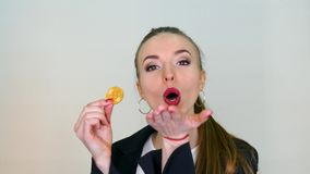 Pretty woman with bitcoin. Pretty business woman hold bitcoin coin. Testing by her tooth stock footage