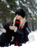 Pretty woman with black dog outdoor in winter Royalty Free Stock Photos