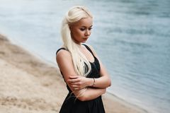 Pretty woman in black dress on the beach. River Royalty Free Stock Image