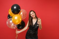 Pretty woman in black dress celebrating looking up holding glass of champagne air balloons isolated on red background