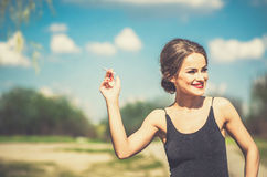 Pretty woman in black dress smoking sigarette outdoor Stock Image