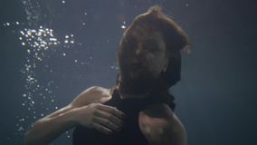 Pretty woman in black dress swimming like mermaid underwater pool. Beautiful woman swimming under water and looking into camera in dark pool stock video