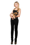 Pretty woman in black pants holding puppy Stock Photo