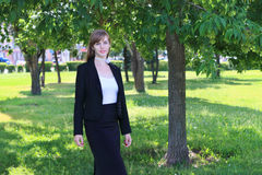 Pretty woman in black suit poses in sunny green park at su Stock Photos