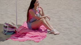 Pretty woman on blanket in shade on beach. Pretty smiling young woman in pink blouse and blue jeans shorts with long brown hair seated in shade at sandy ocean stock footage