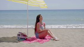 Pretty woman on blanket under beach umbrella. Pretty smiling woman in pink shirt and blue jeans shorts with long brown hair seated in shade under yellow umbrella stock video footage