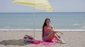Pretty woman on blanket under beach umbrella. Pretty smiling woman in pink shirt and blue jeans shorts with long brown hair seated in shade under yellow umbrella stock footage