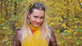 Pretty woman blinks her eyes and smiles in forest in autumn. Pretty female blinks her eyes and smiles in a forest on background of trees with yellow foliage in stock footage
