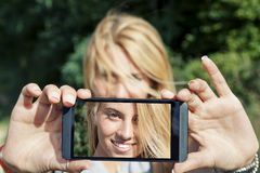 Pretty woman with blond hair take a selfie. With smart phone Stock Photos