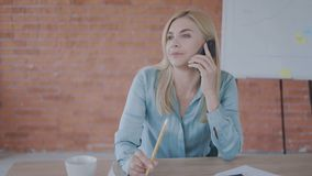 Pretty woman blonde economist talking on the phone in the office. office work concept 4K