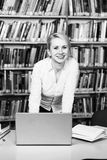 Student Learning in Library. Pretty Woman With Blonde Hair in the Library - Laptop and Organiser on the Table - Looking at the Screen a Concept of Studying Royalty Free Stock Images