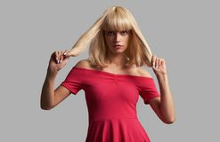 Pretty woman in blonde wig and red dress. Isolated stock image