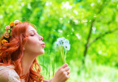 Pretty woman blowing on dandelion royalty free stock image