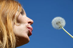 Pretty woman blowing seeds Royalty Free Stock Images