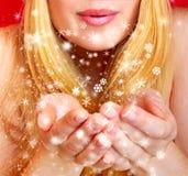 Pretty woman blowing snowflakes Stock Photo