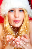 Pretty woman blowing snowflakes Stock Images