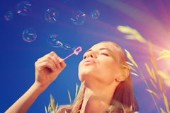 Pretty woman blowing soap bubbles Stock Images