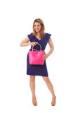 Pretty woman in blue dress posing with bright tote bag.Isolated. Pretty woman in blue dress posing with bright magenta wicker magenta tote bag.Isolated on the Stock Images