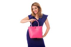 Pretty woman in blue dress posing with bright tote bag.Isolated. Pretty woman in blue dress posing with bright wicker magenta tote bag.Isolated on the white Stock Image