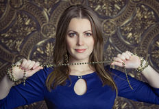 Pretty woman in blue dress. Young pretty woman in blue dress holding goldy chaplet Stock Images