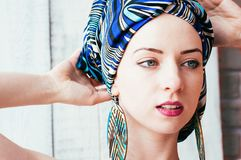 A pretty woman in a blue headscarf in an african manner stock images