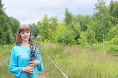 Pretty woman in blue holds chicory flowers Stock Photos