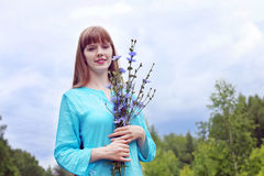 Pretty woman in blue holds chicory flowers and smiles Stock Photos