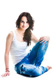 Pretty woman in blue jeans sitting on white floor Stock Photos