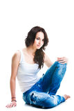 Pretty woman in blue jeans sitting on white floor Royalty Free Stock Photography