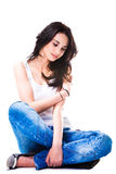 Pretty woman in blue jeans sitting on white floor Royalty Free Stock Image